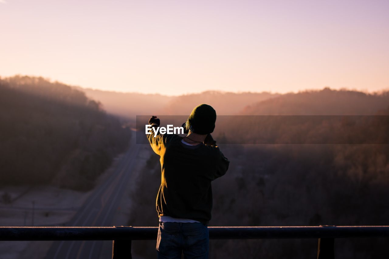 Man Looking At View At Sunset