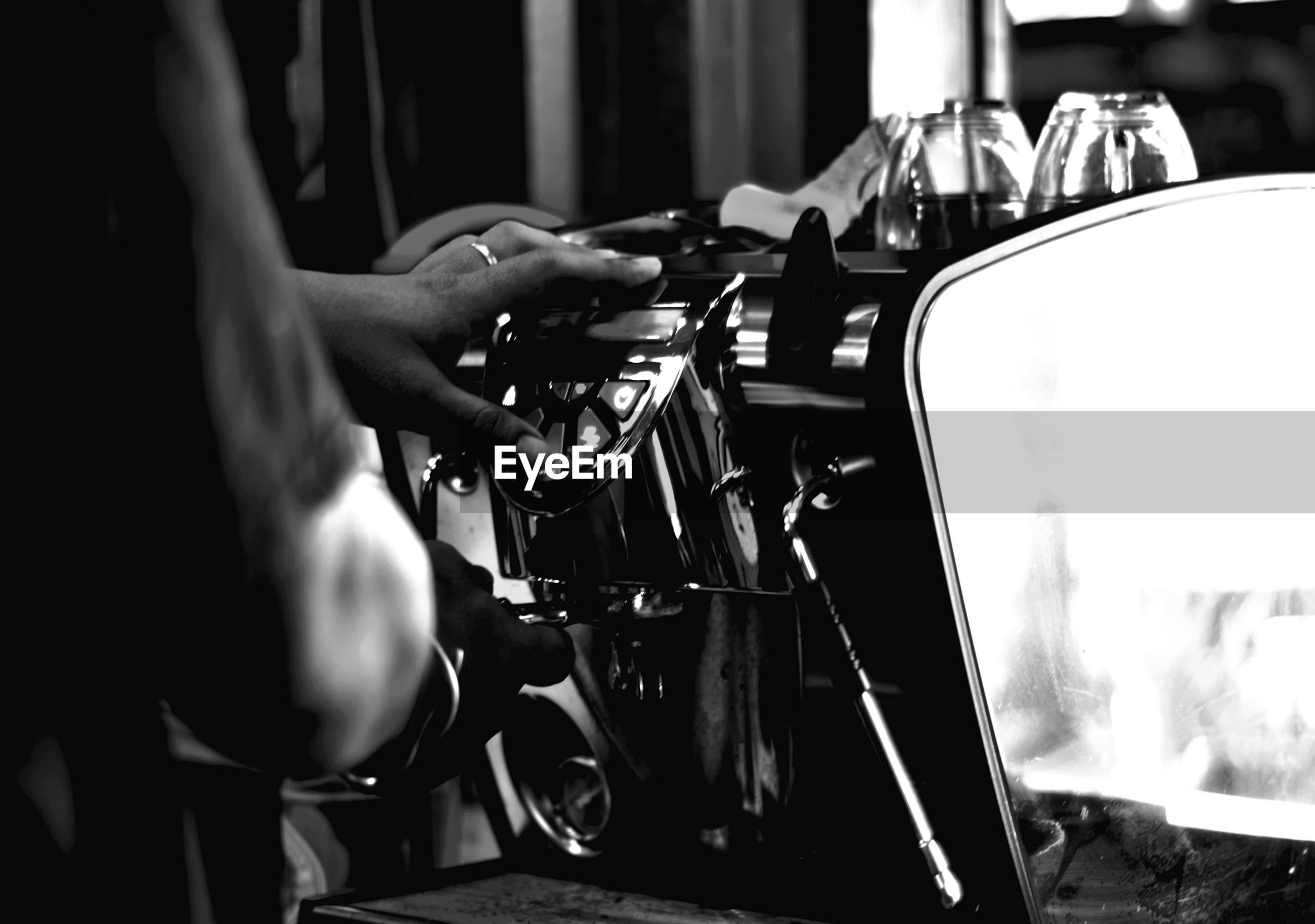 Behind shot of barista made to coffee by coffee machine for service to customer