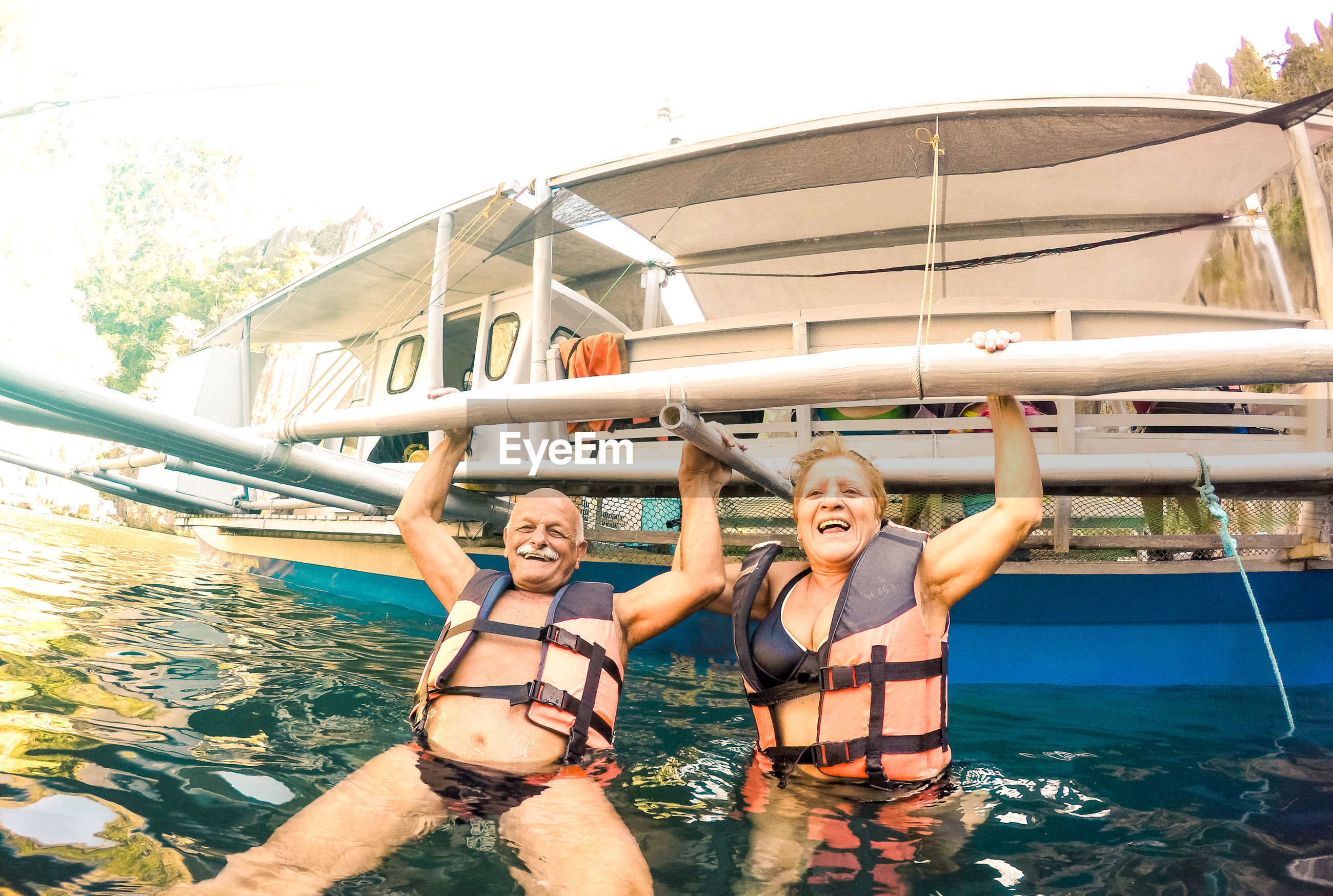 Portrait of happy couple holding metal while swimming in sea