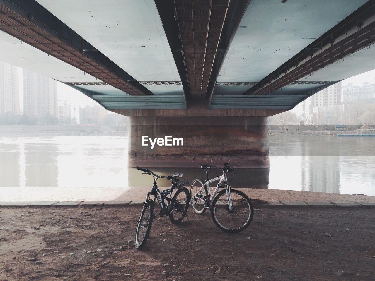 Bicycles Under Bridge Over River