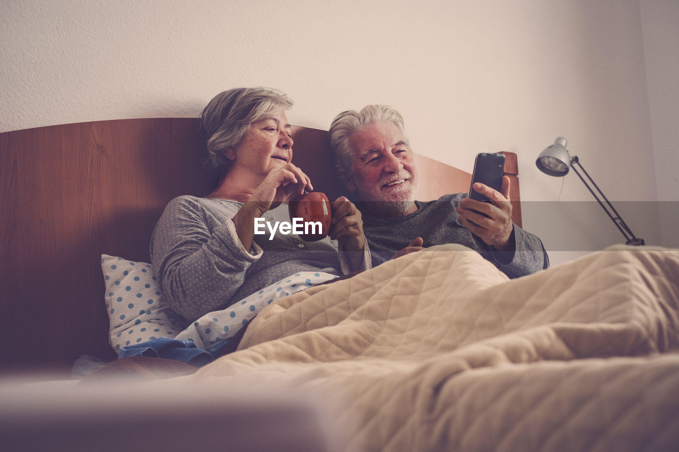 Senior couple looking at mobile phone while relaxing on bed at home