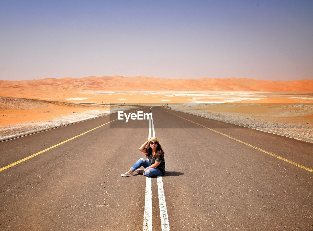Full length of woman sitting on country road amidst desert during summer