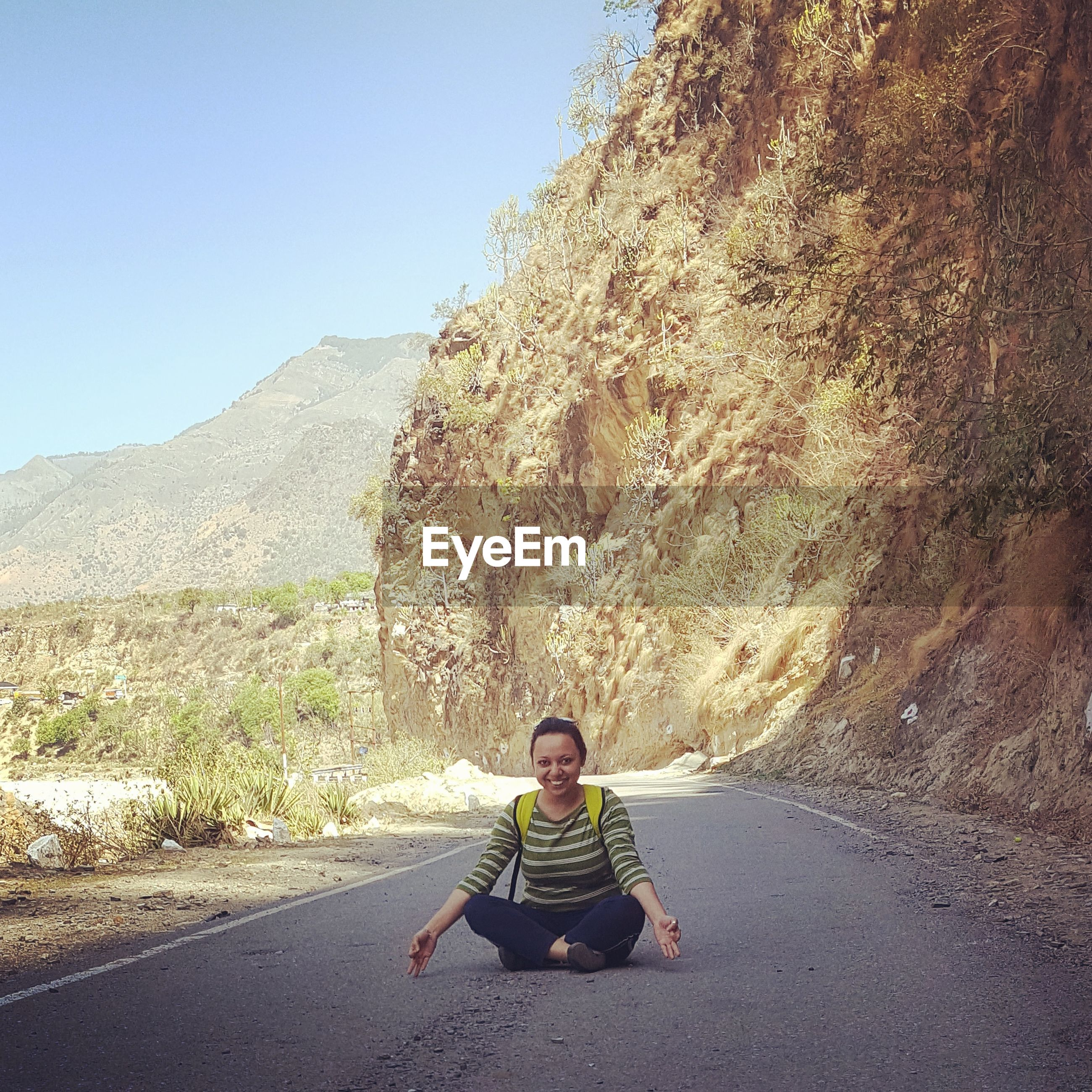 Portrait of smiling woman doing yoga on road against mountains