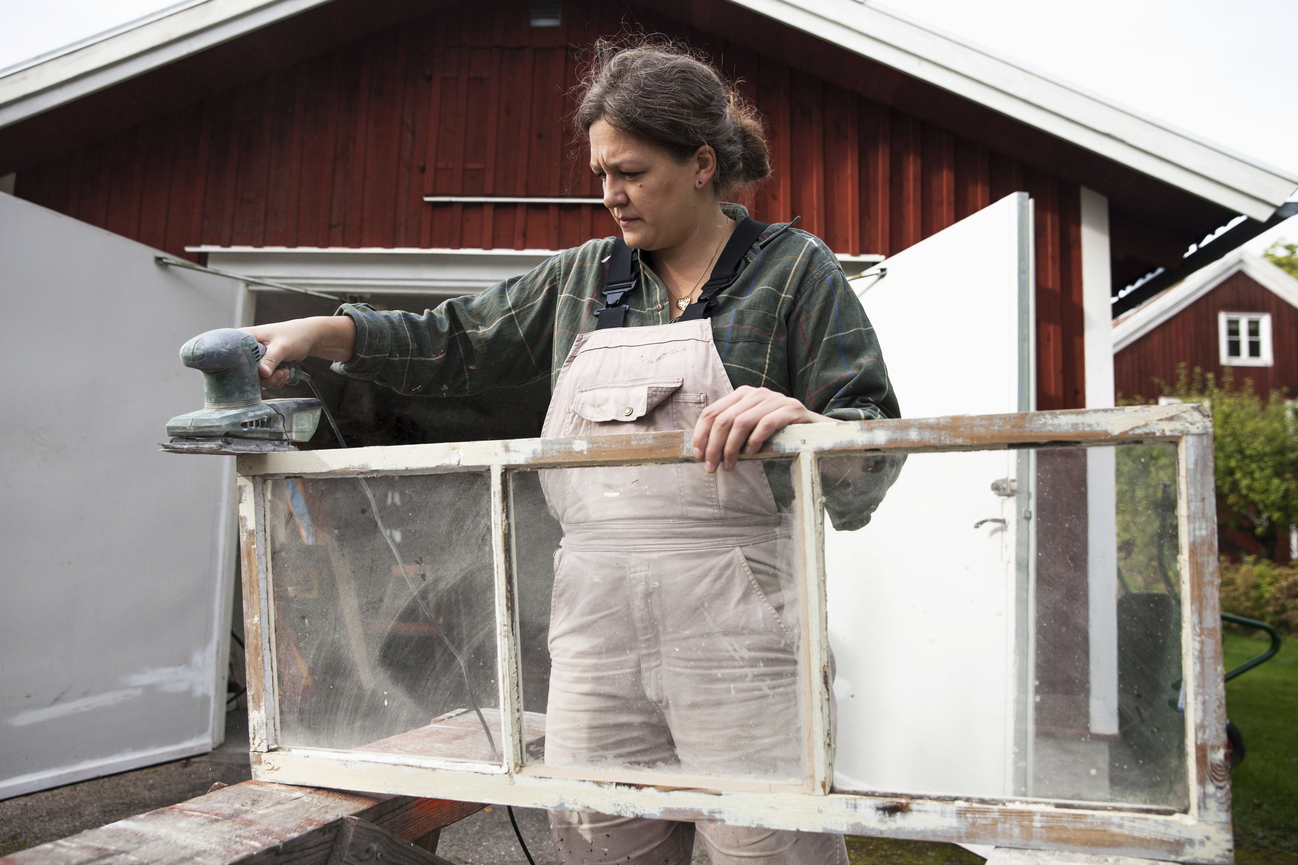 Female upholsterer using sander on window frame outside workshop