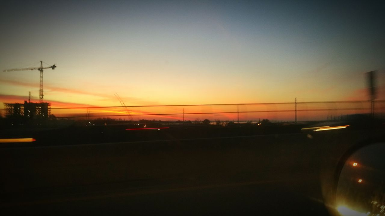 sunset, transportation, car, land vehicle, mode of transport, road, orange color, no people, sky, travel, silhouette, city, outdoors, car point of view, illuminated, nature, architecture, day