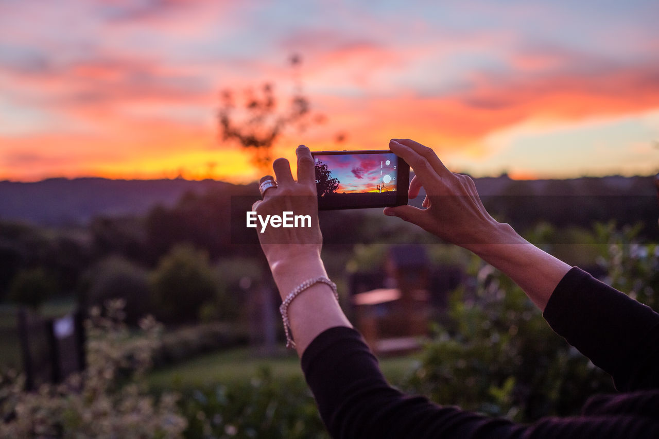 WOMAN PHOTOGRAPHING THROUGH SMART PHONE IN SUNSET