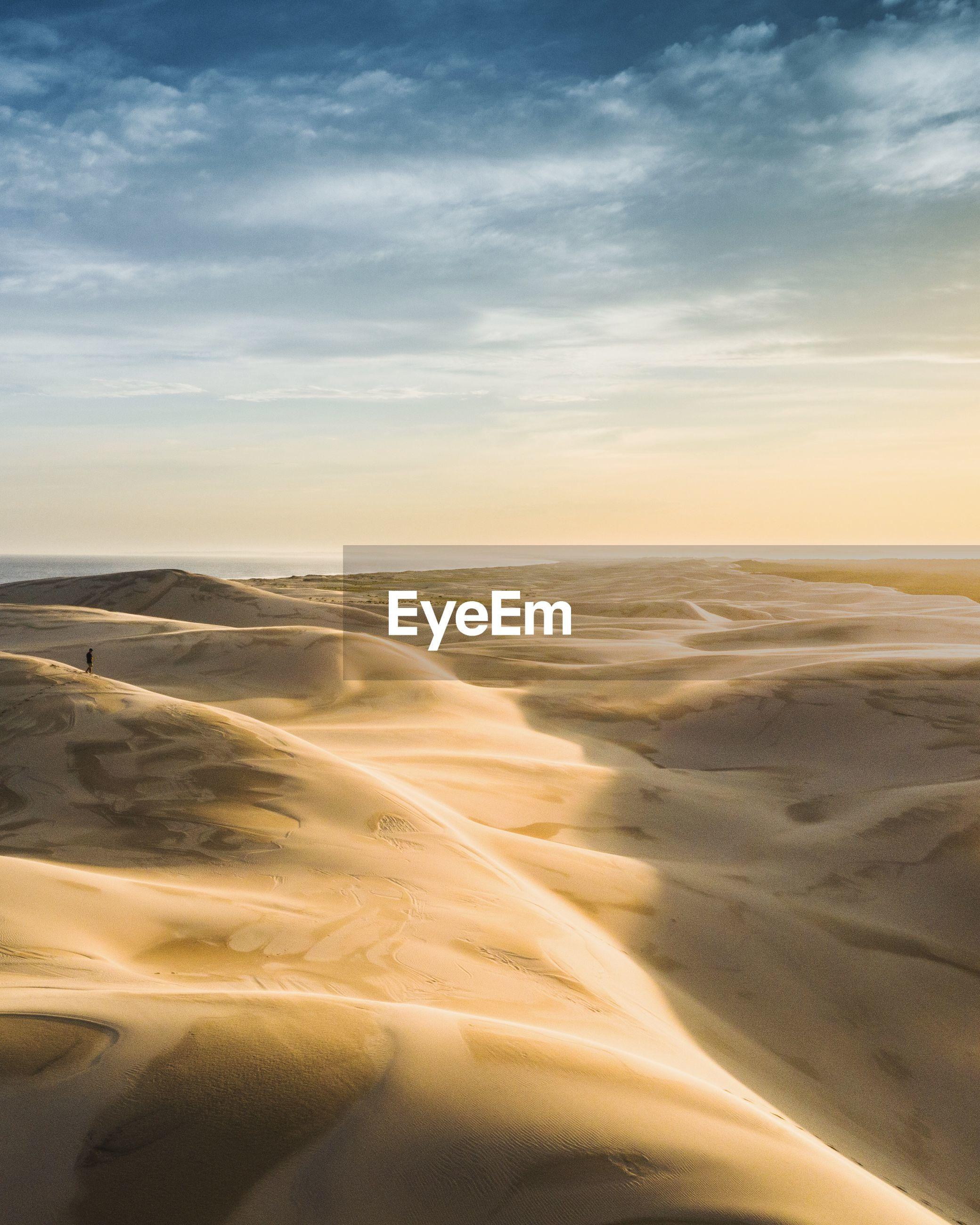 VIEW OF DESERT AGAINST SKY DURING SUNSET