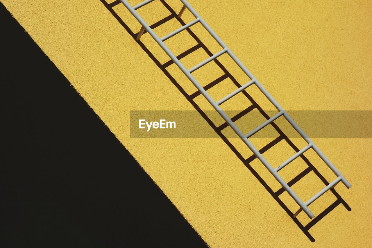Close-Up Of Ladder On Yellow Wall