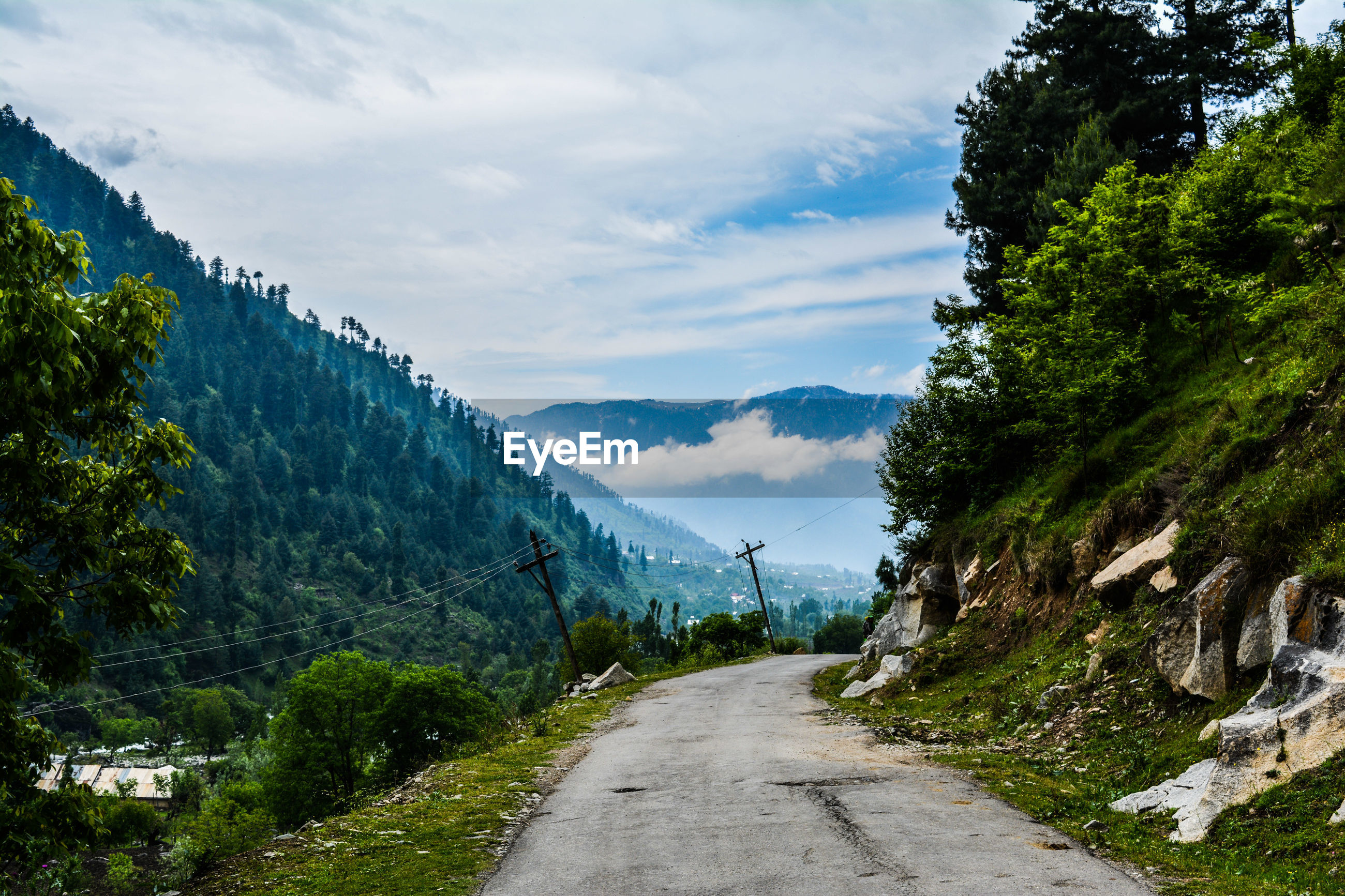 ROAD AMIDST TREES AND MOUNTAIN AGAINST SKY