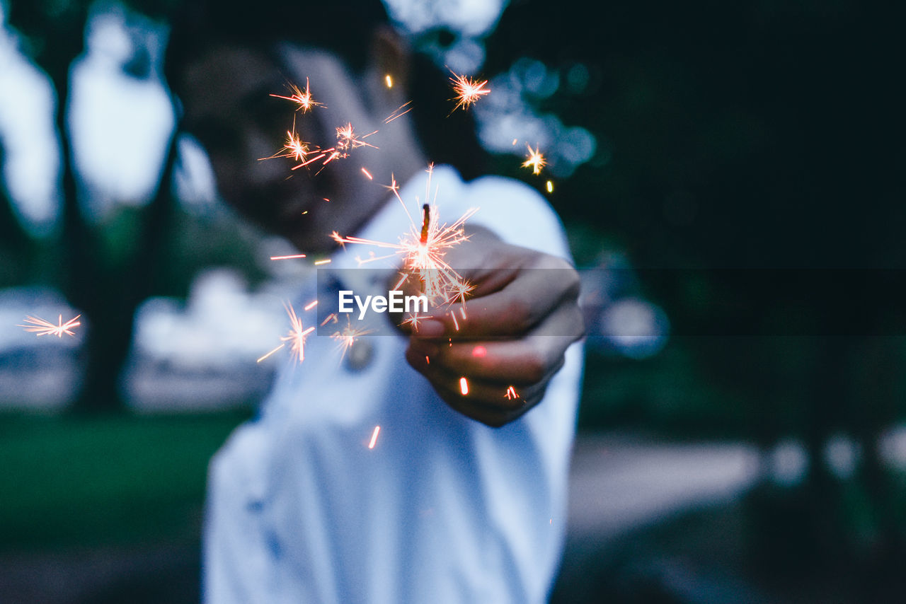Woman with burning sparkler against trees