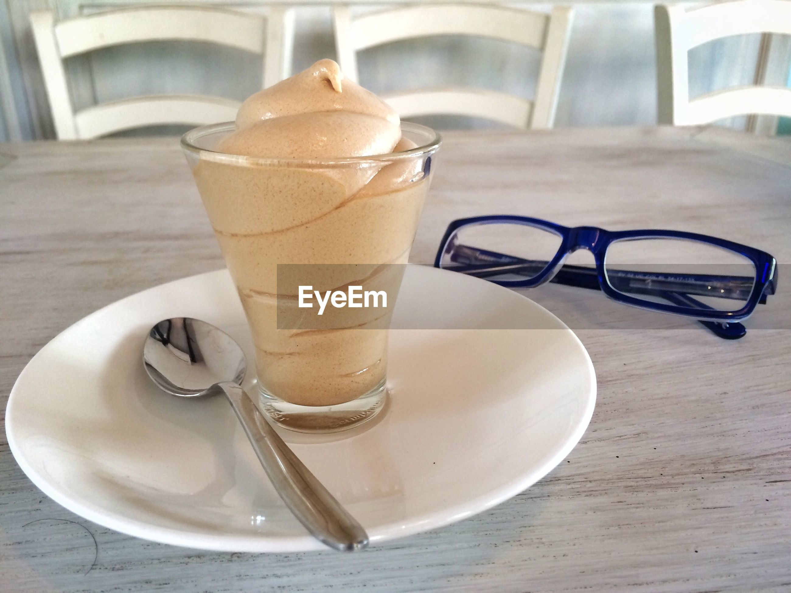 Close-up of coffee with eyeglass on table in cafe