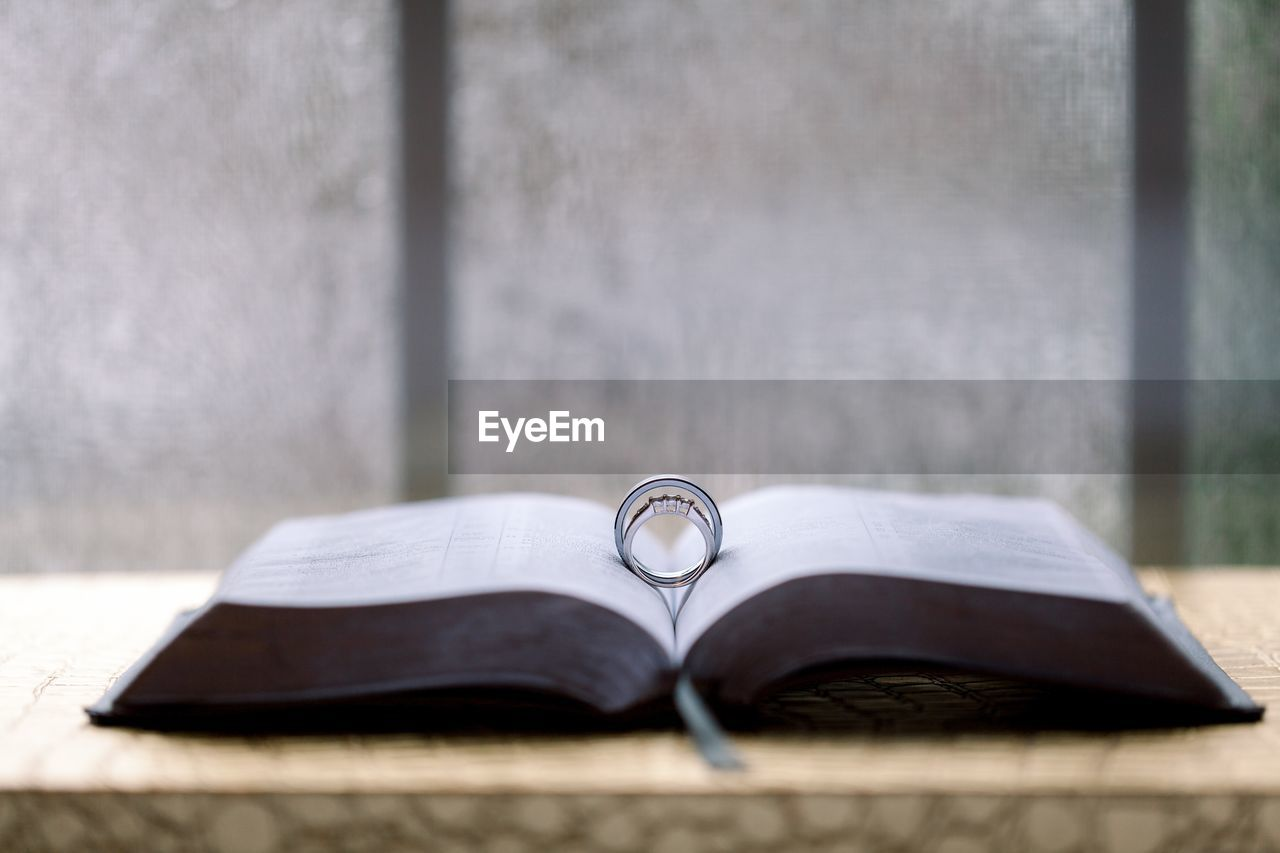 publication, book, day, still life, open, no people, focus on foreground, selective focus, education, close-up, absence, table, indoors, literature, personal accessory, two objects, glasses, wood - material, paper