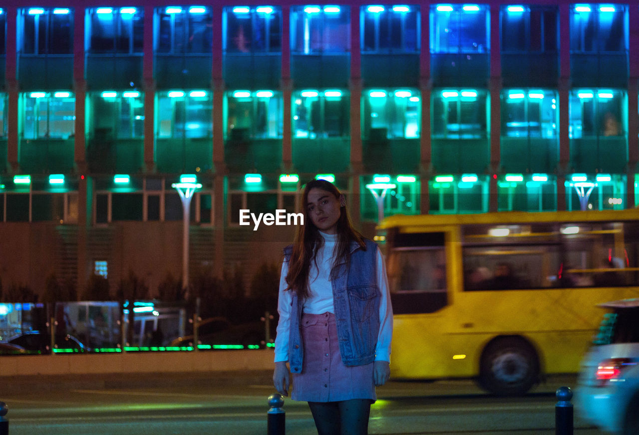 Portrait of young woman walking on city street at night