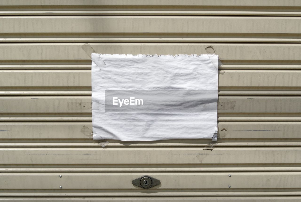 Close-Up Of Blank White Paper On Closed Shutter