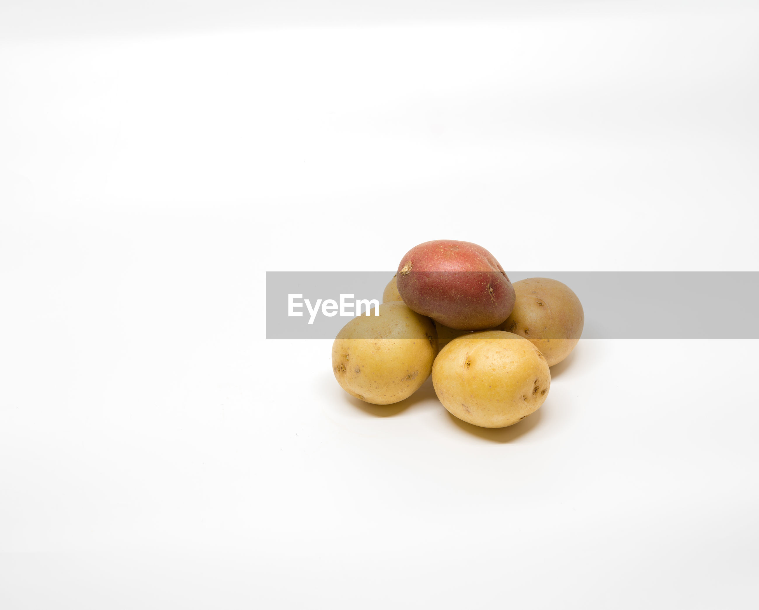 Small group of small potatoes on a white background with copy space.