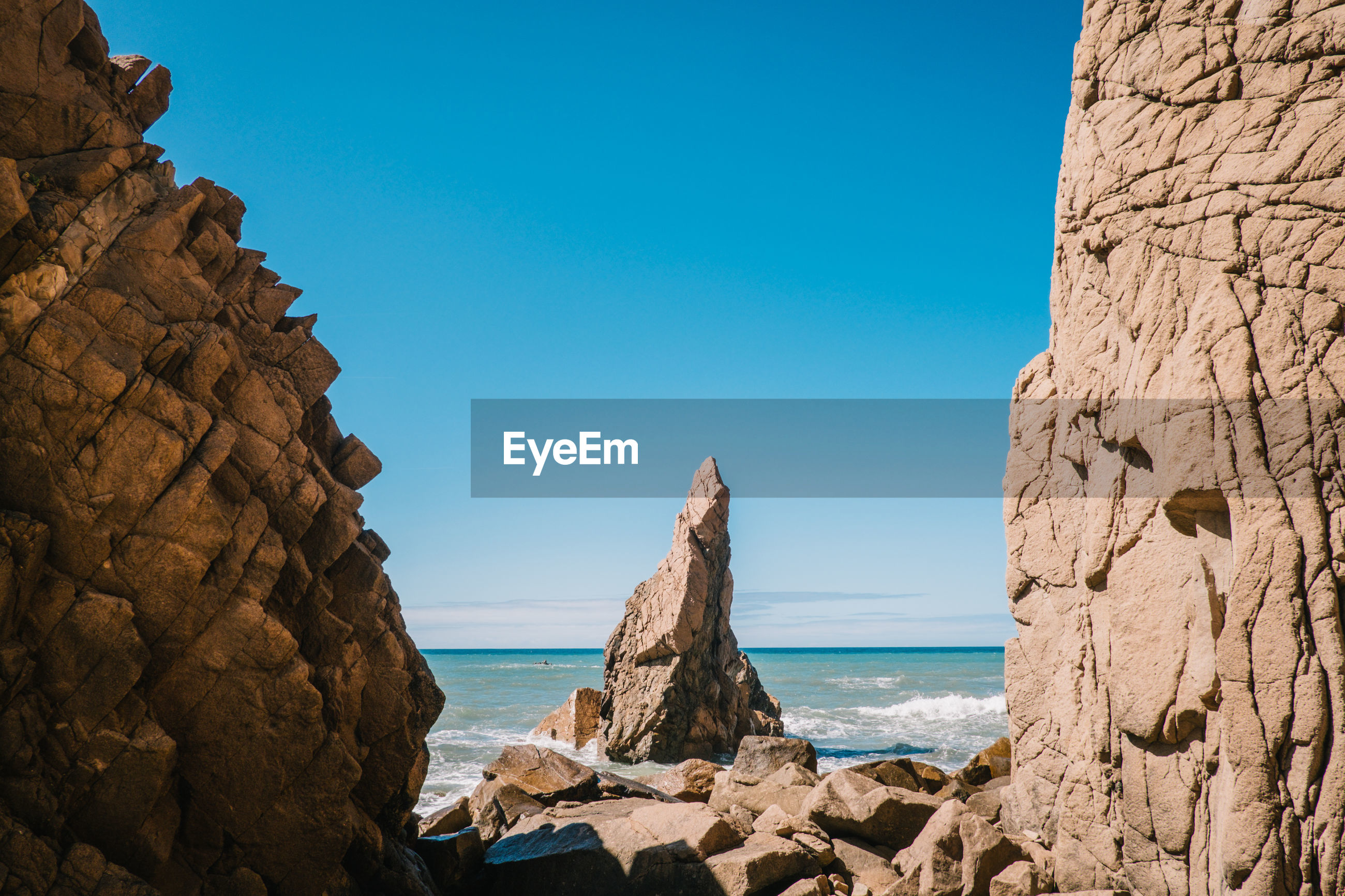 Rock formations at beach against blue sky