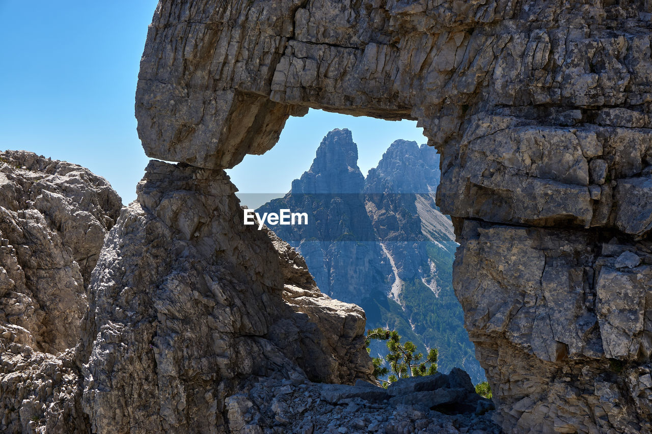 rock, mountain, rock - object, solid, rock formation, nature, sky, scenics - nature, no people, beauty in nature, tranquility, arch, day, mountain range, clear sky, physical geography, tranquil scene, geology, non-urban scene, travel, outdoors, natural arch, mountain peak, formation, eroded