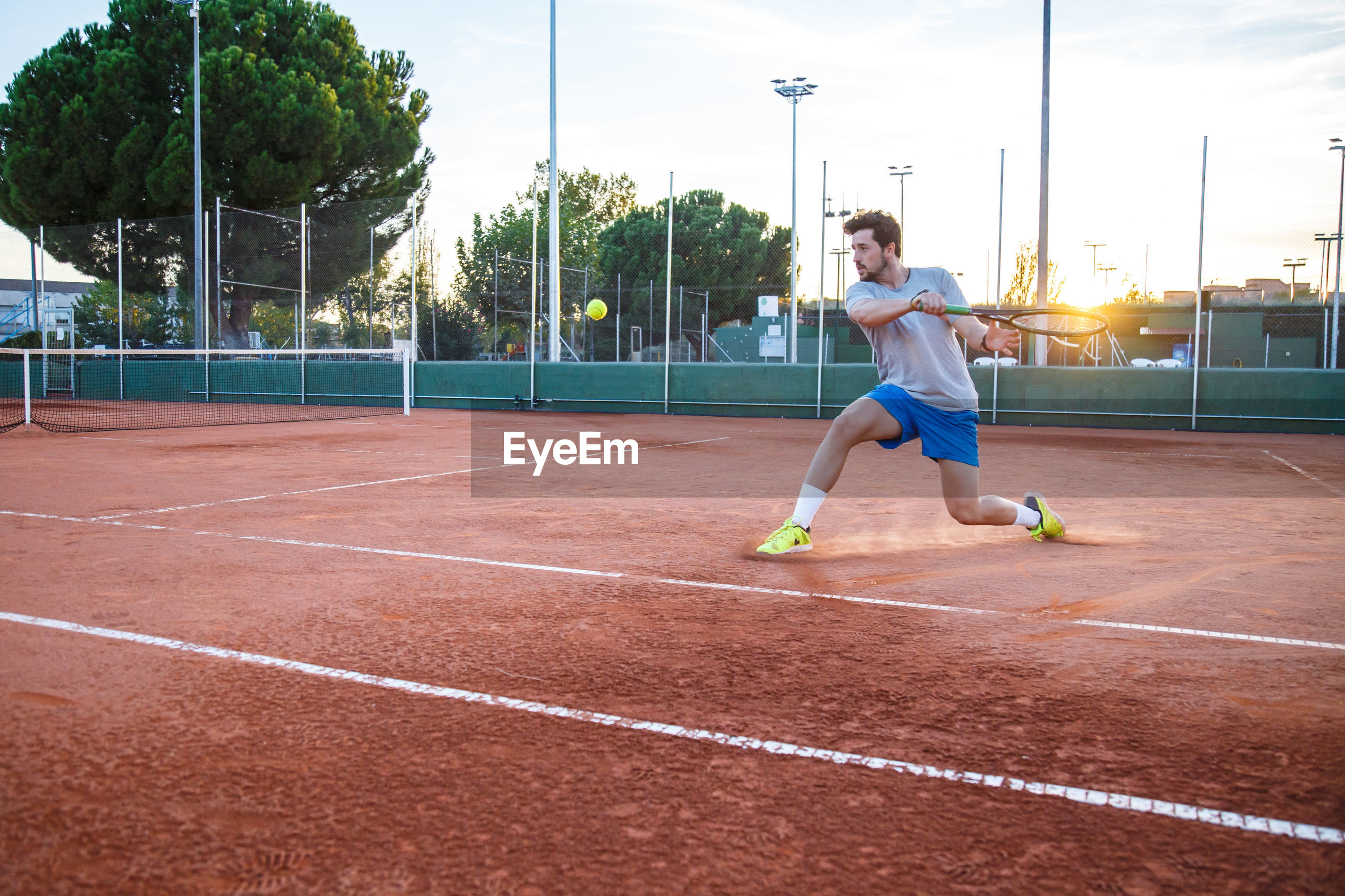 Full length of young man playing tennis on field