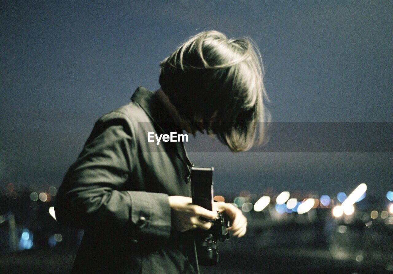 Side View Of Woman Holding Camera Against Sky At Night