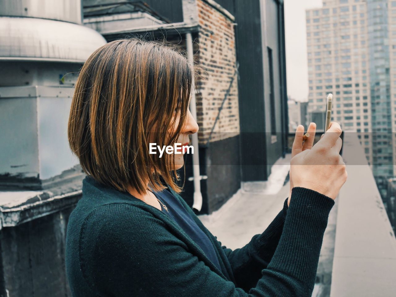 Woman Taking Photo With Smart Phone From Rooftop Balcony