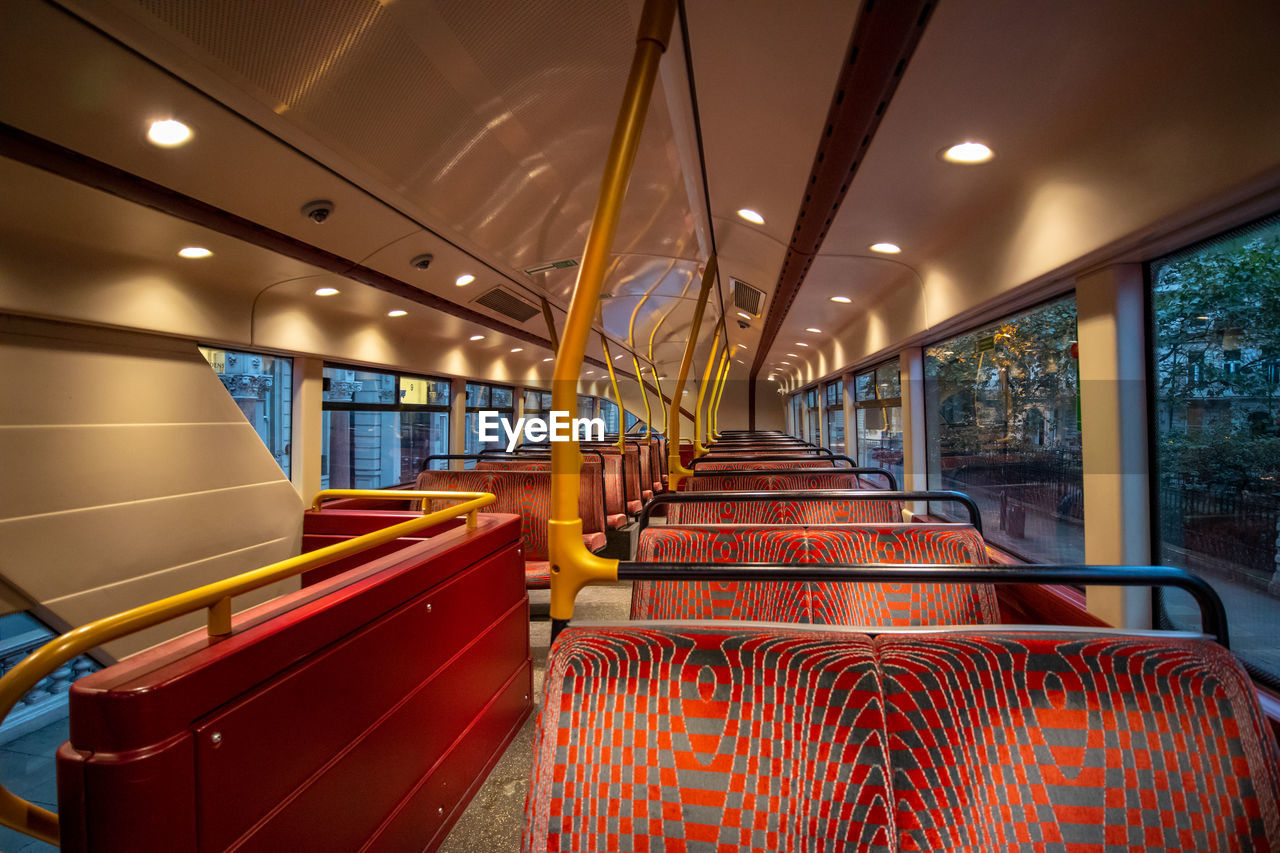 seat, mode of transportation, vehicle interior, transportation, empty, vehicle seat, public transportation, absence, no people, indoors, illuminated, rail transportation, window, train, land vehicle, in a row, bus, lighting equipment, red, day, ceiling, luxury