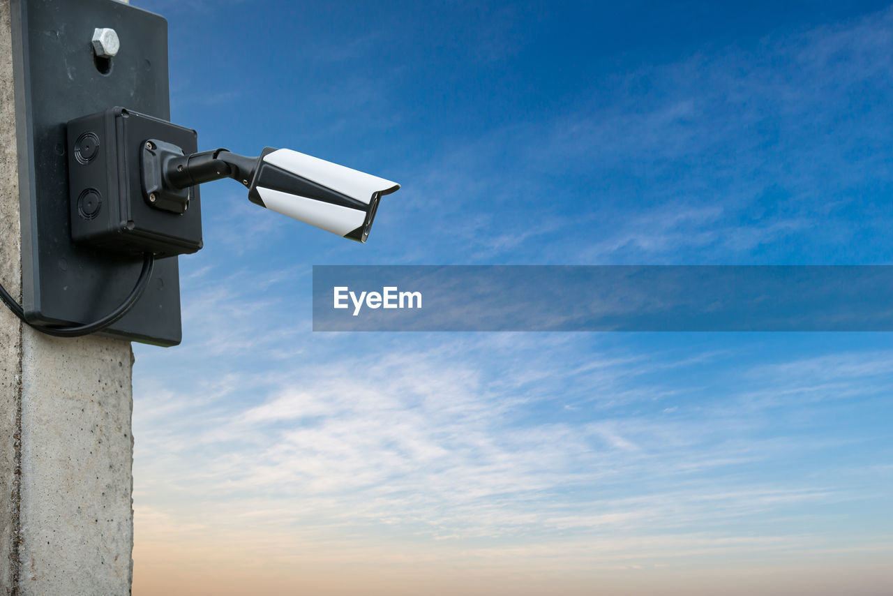 Low Angle View Of Security Camera Against Sky During Sunset