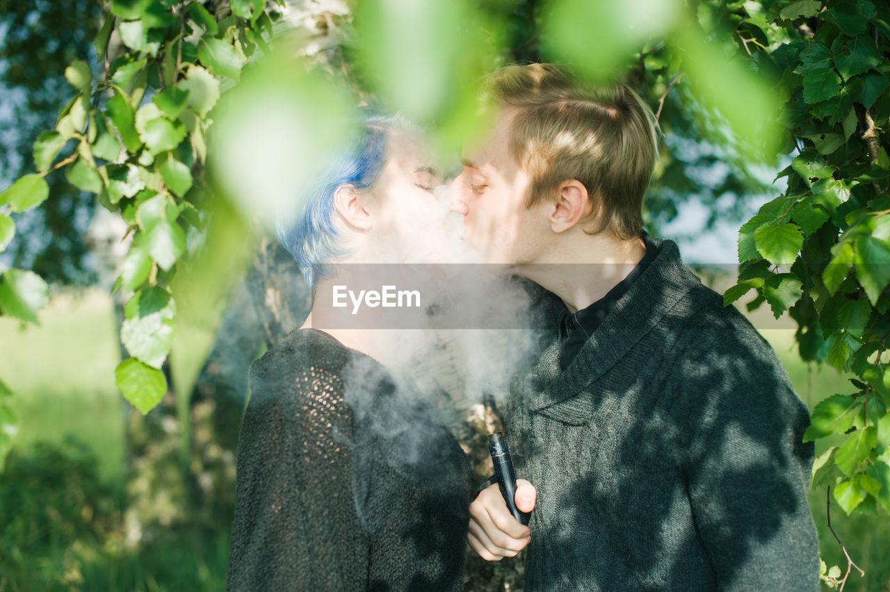 Young couple kissing while exhaling smoke