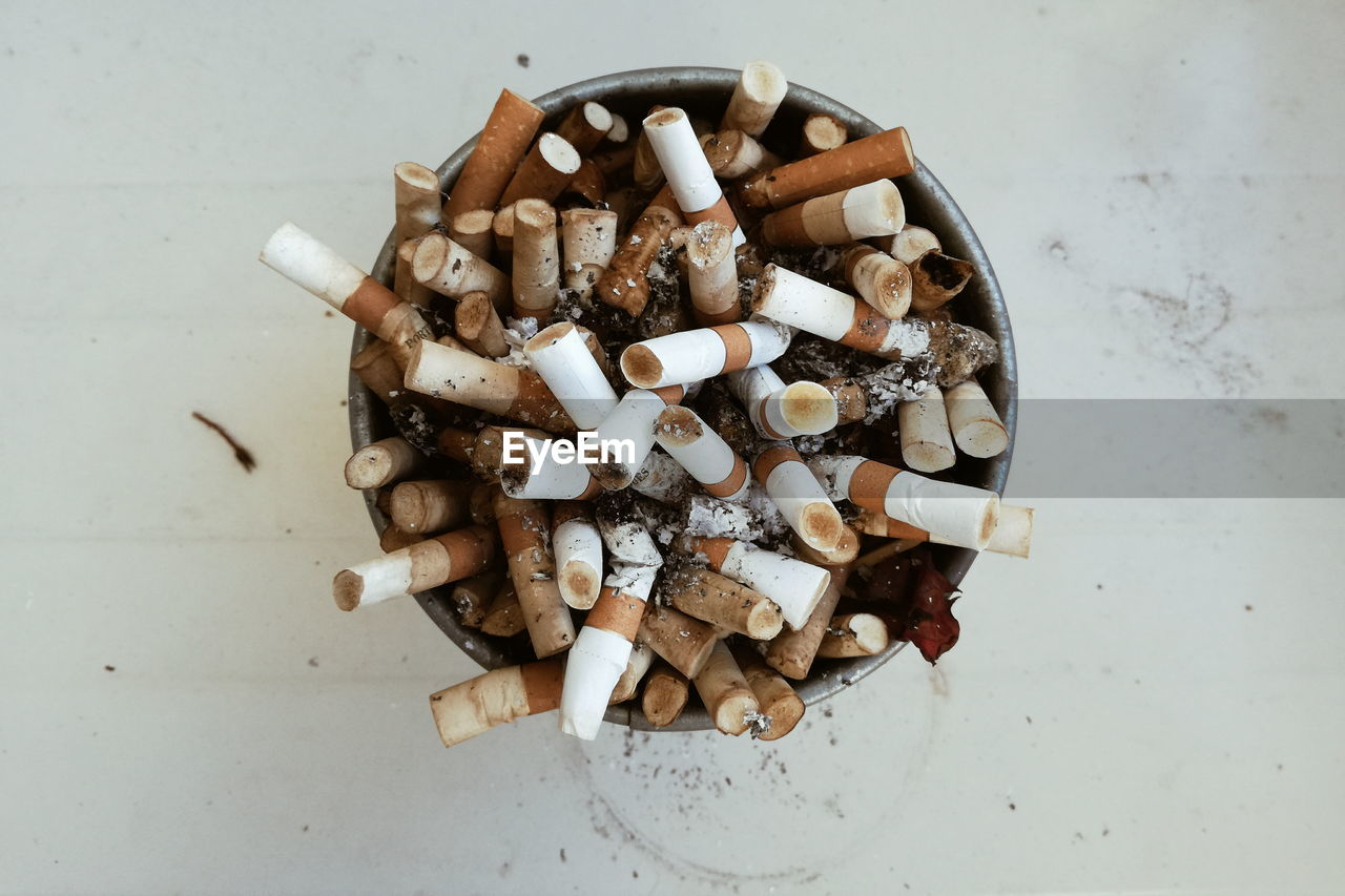 Directly above shot of cigarette butts in ashtray on table