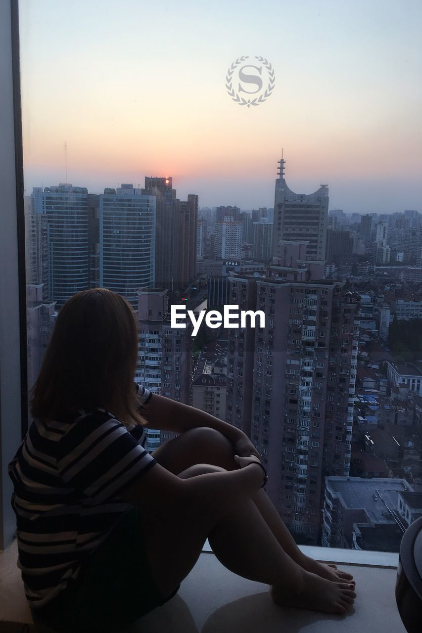 architecture, skyscraper, building exterior, real people, cityscape, built structure, rear view, city, one person, urban skyline, lifestyles, sunset, leisure activity, women, outdoors, day, sky, young adult, people