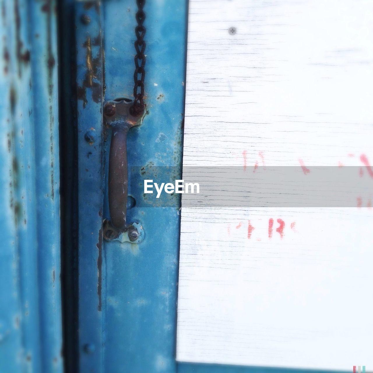 Close-up of paper stuck on blue door