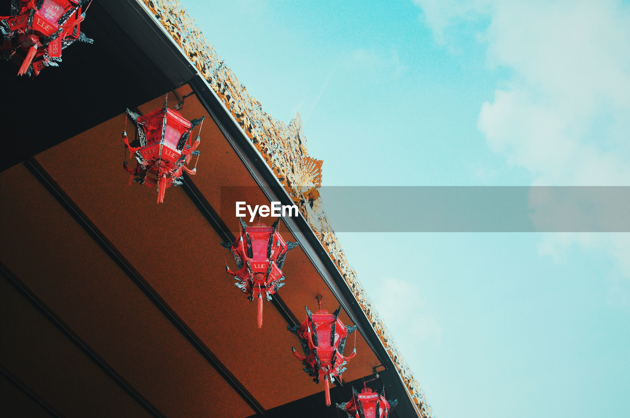 Low angle view of lanterns hanging over roof against sky