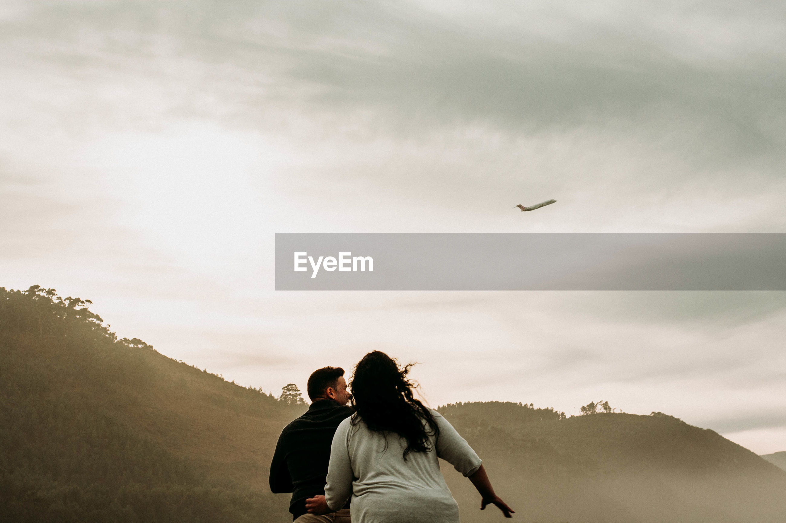 REAR VIEW OF COUPLE FLYING IN SKY