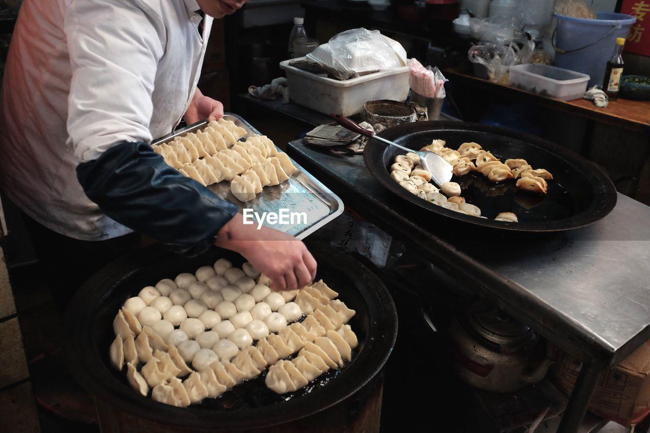 Chef frying jiaozi in kitchen