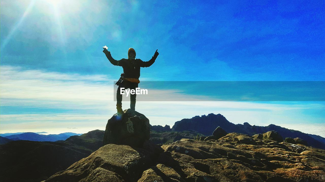 sky, arms raised, sunbeam, standing, nature, rock - object, cloud - sky, full length, scenics, one person, real people, outdoors, mountain, beauty in nature, arms outstretched, tranquility, day, low angle view, tranquil scene, men, sunlight, blue, leisure activity, lifestyles, mountain range, landscape, energetic, human hand, people
