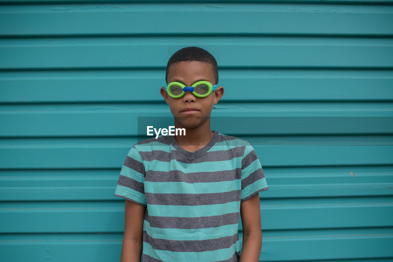 Portrait Of Boy In Swimming Goggles Standing Against Shutter