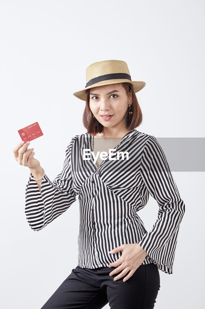 one person, hat, studio shot, white background, young adult, clothing, striped, young women, indoors, standing, looking at camera, portrait, casual clothing, three quarter length, front view, holding, smiling, beauty, cut out, beautiful woman, hairstyle