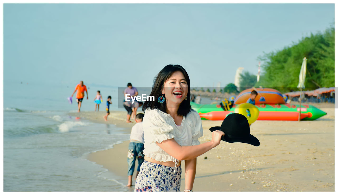 real people, leisure activity, lifestyles, beach, land, portrait, incidental people, sky, one person, smiling, enjoyment, happiness, nature, auto post production filter, standing, emotion, holding, transfer print, water, outdoors, hairstyle
