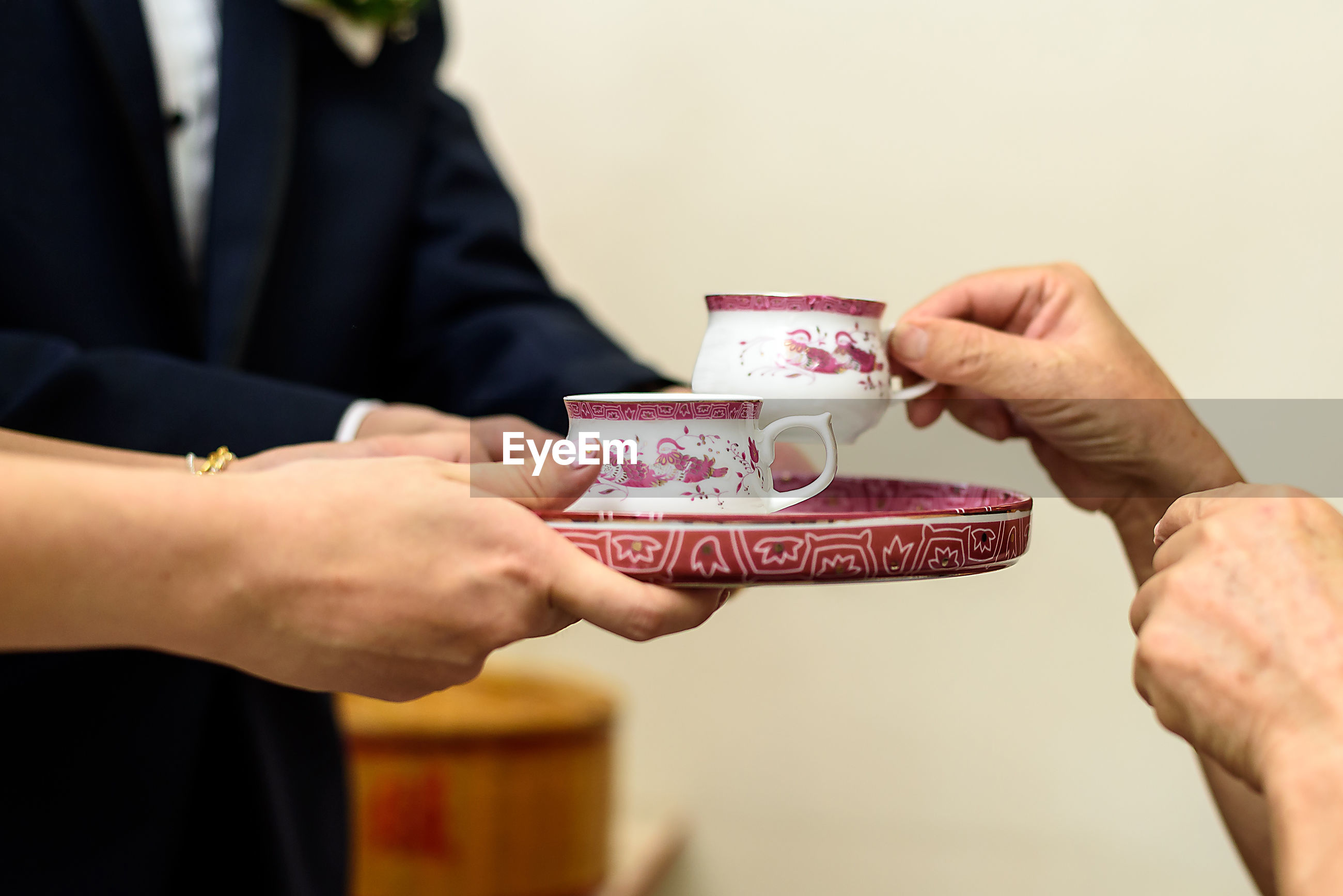 Cropped hands of woman serving drink to guest during tea ceremony