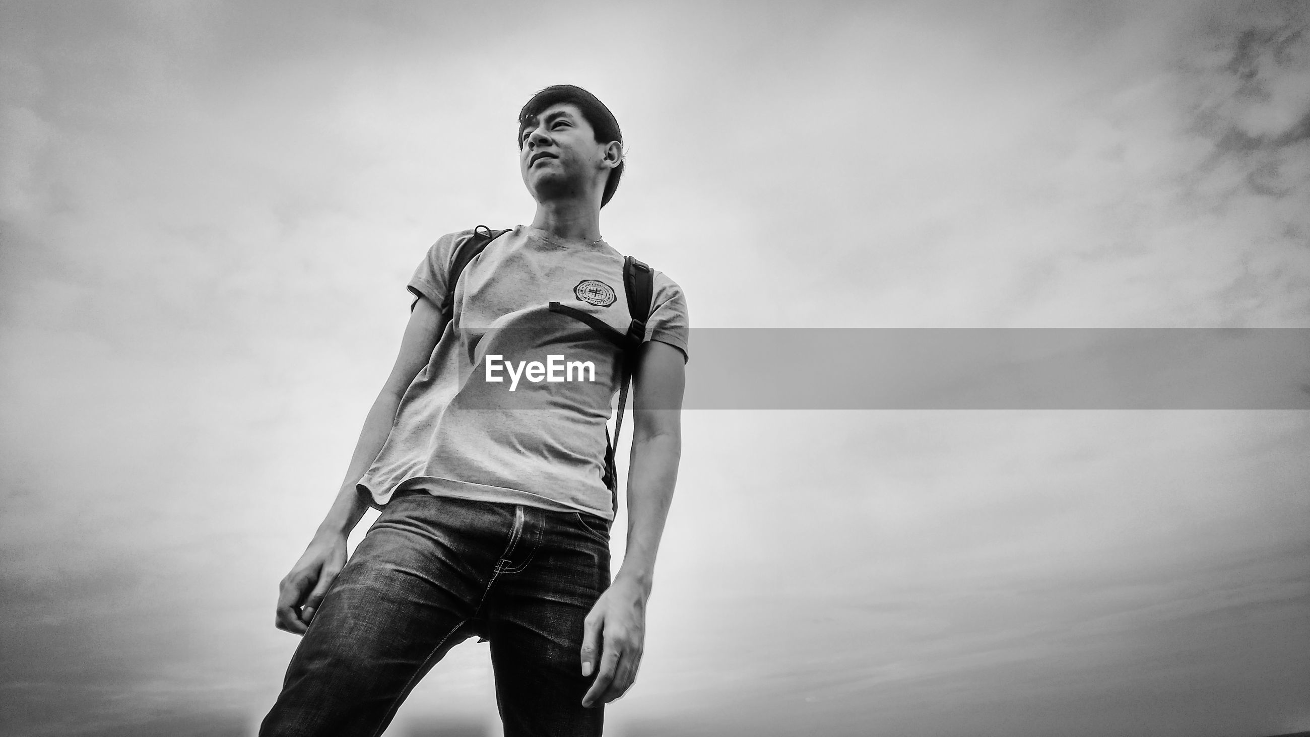 Low angle view of young man looking away while standing against cloudy sky