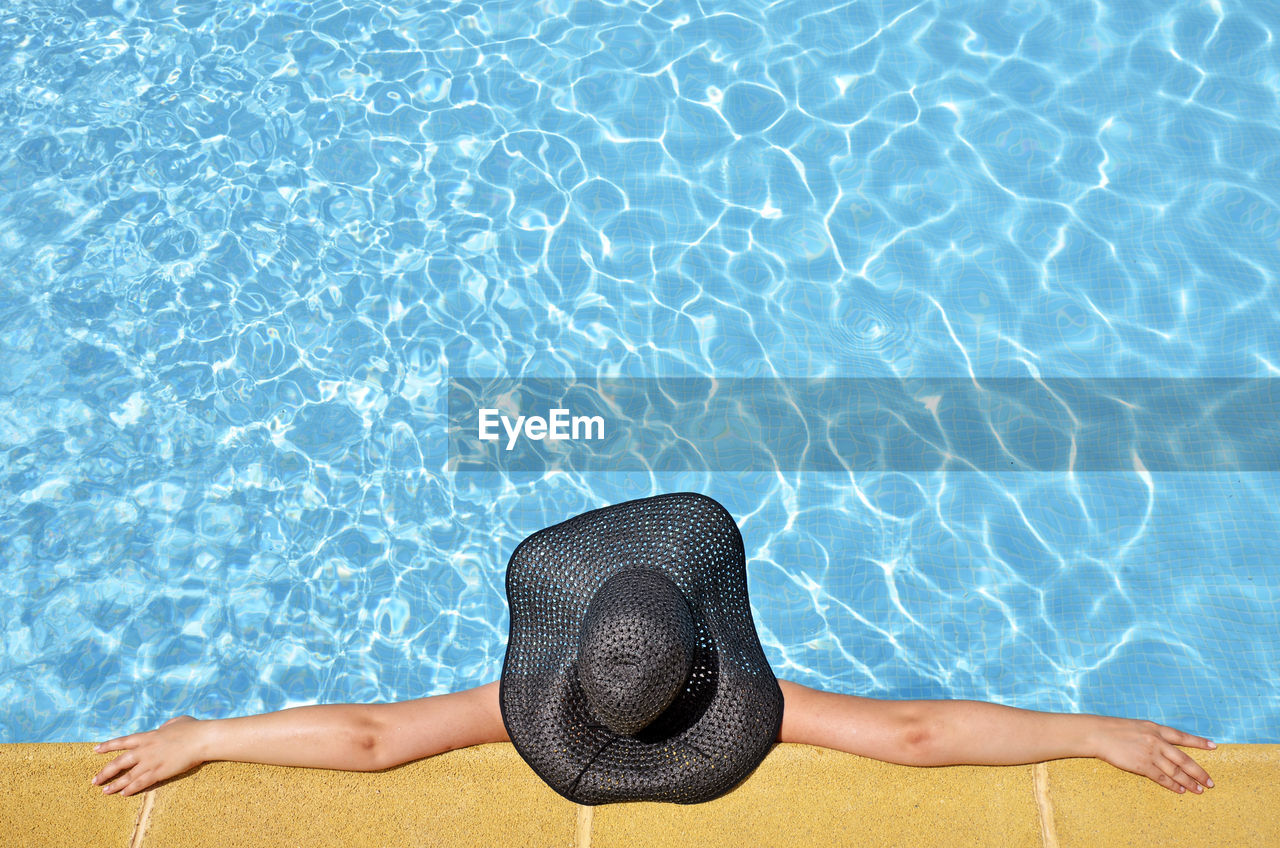 Directly Above Shot Of Woman With Black Hat Relaxing In Swimming Pool