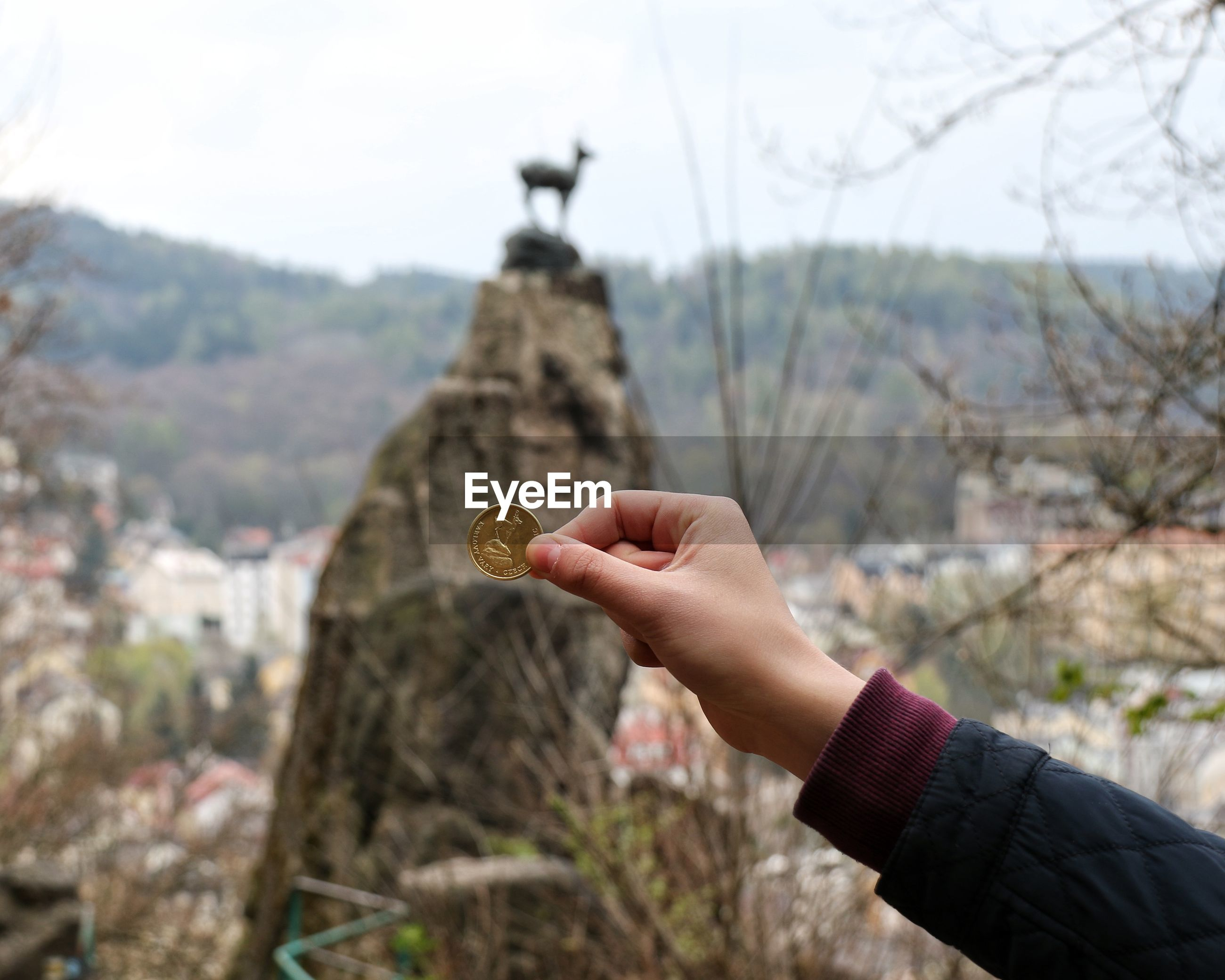 Close-up of hand holding coin against rock formation