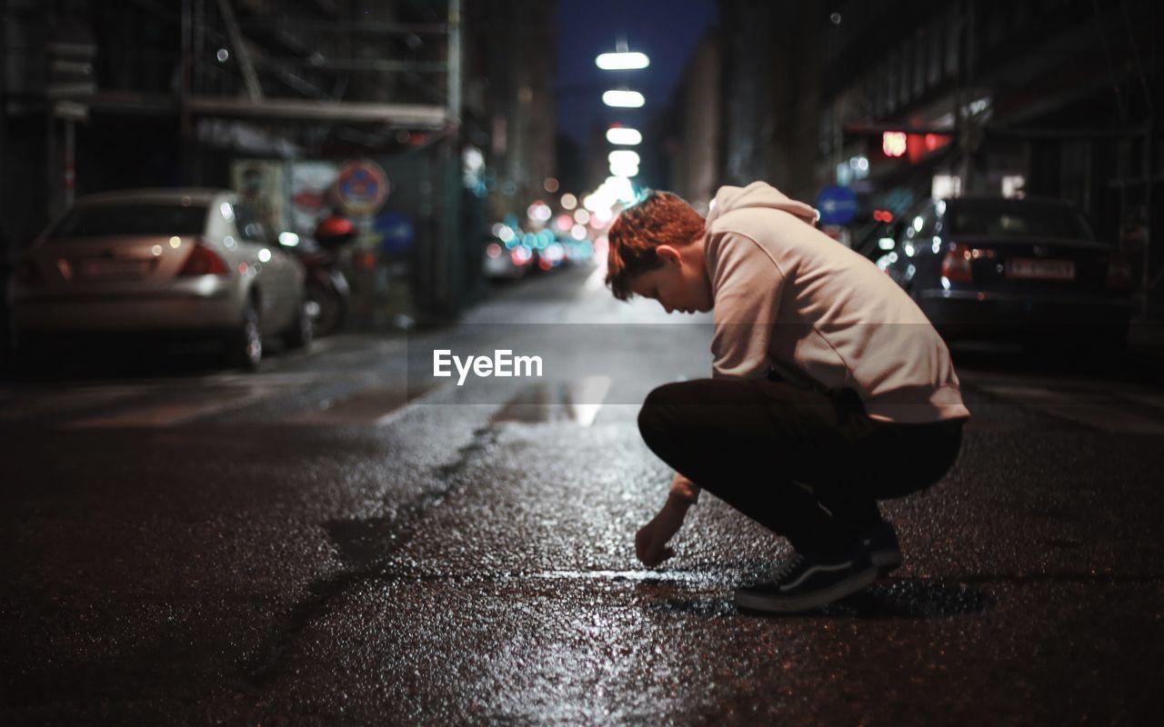 SIDE VIEW OF MAN ON ILLUMINATED STREET
