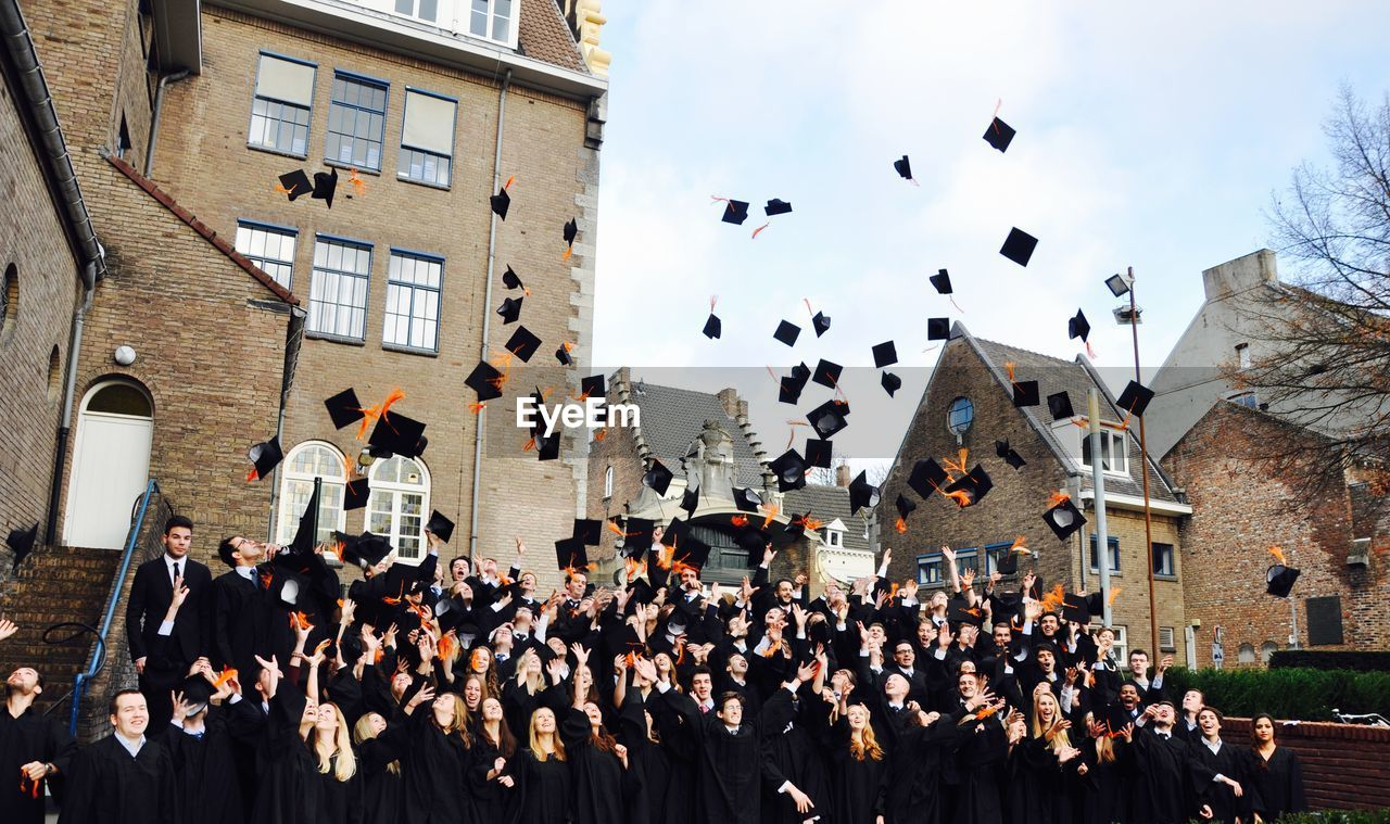 Students Throwing Mortarboards In Air Against Sky