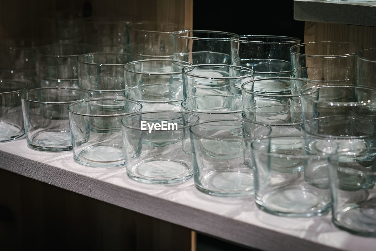 glass - material, glass, transparent, drinking glass, household equipment, table, indoors, no people, empty, arrangement, still life, close-up, side by side, group of objects, in a row, large group of objects, focus on foreground, group, order, tray