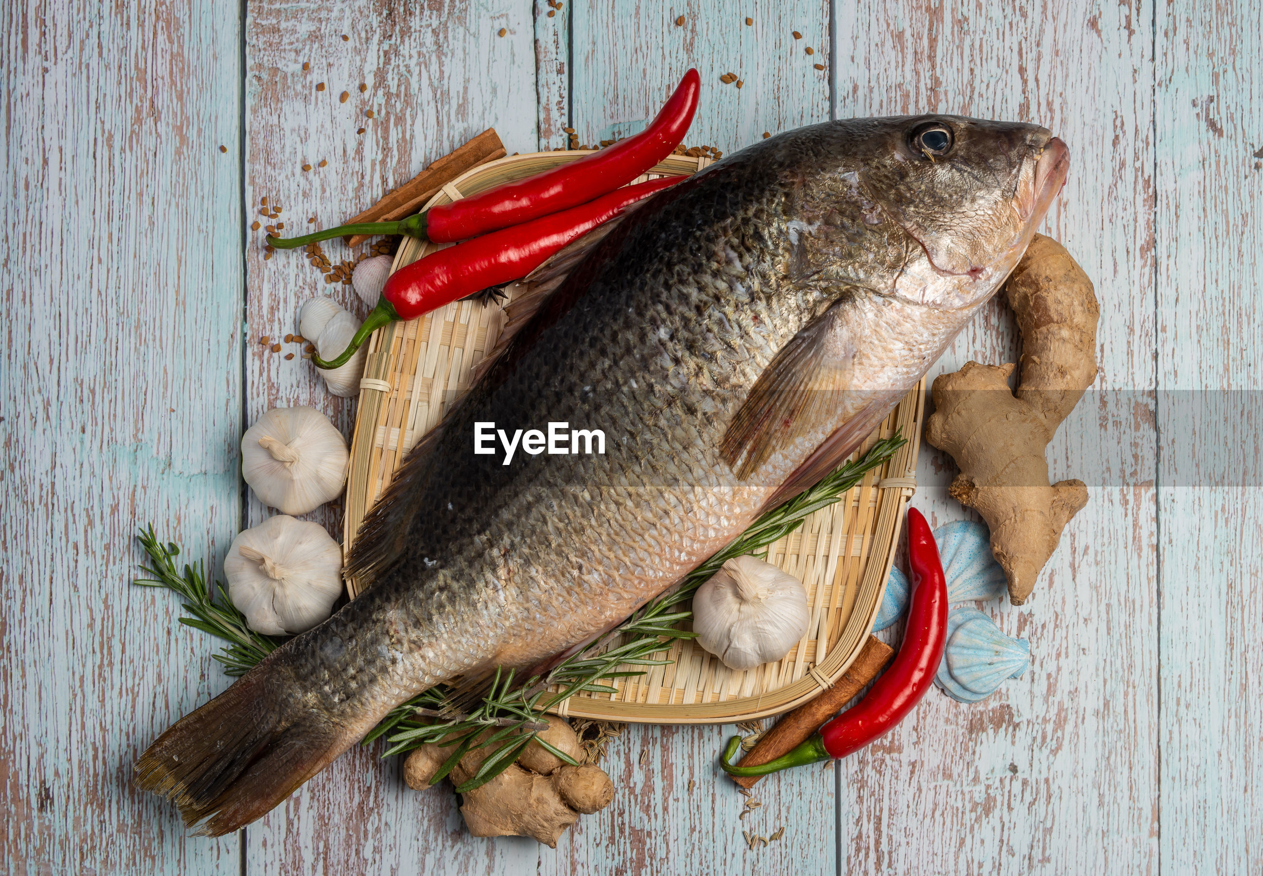 HIGH ANGLE VIEW OF DEAD FISH ON TABLE AGAINST WALL
