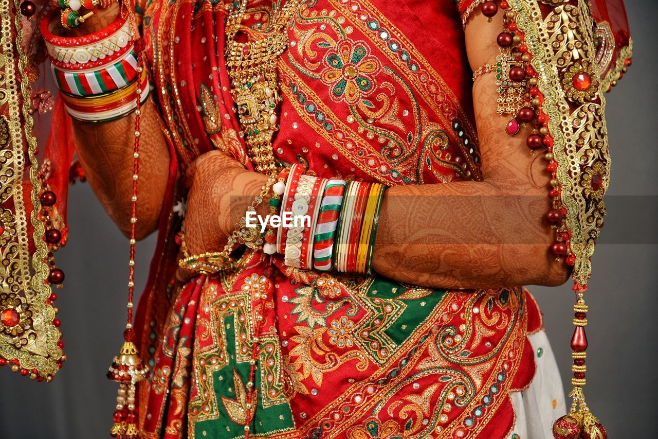 traditional clothing, adult, real people, midsection, indoors, one person, clothing, red, wedding, life events, close-up, women, pattern, celebration, lifestyles, henna tattoo, hand, wedding ceremony