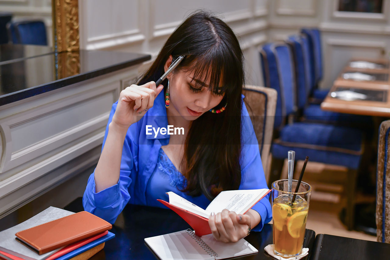Young woman reading book by drink on table