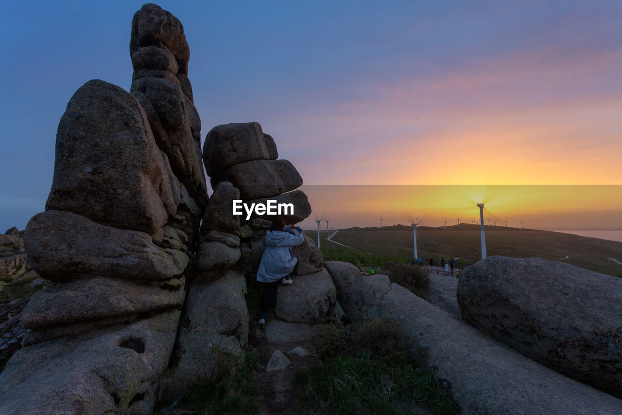 REAR VIEW OF STATUE AGAINST ROCK DURING SUNSET