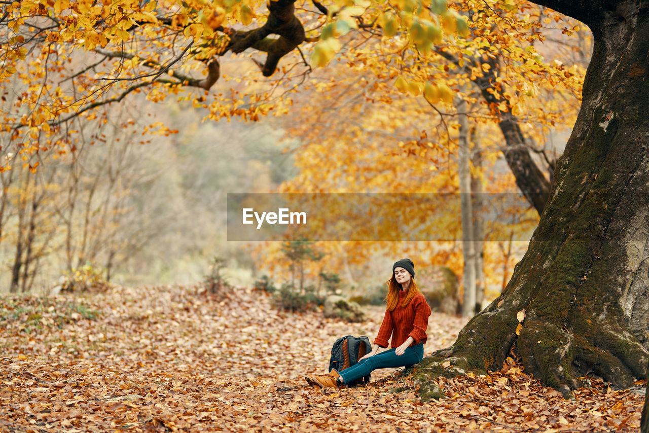 FULL LENGTH OF YOUNG WOMAN SITTING ON LAND IN FOREST