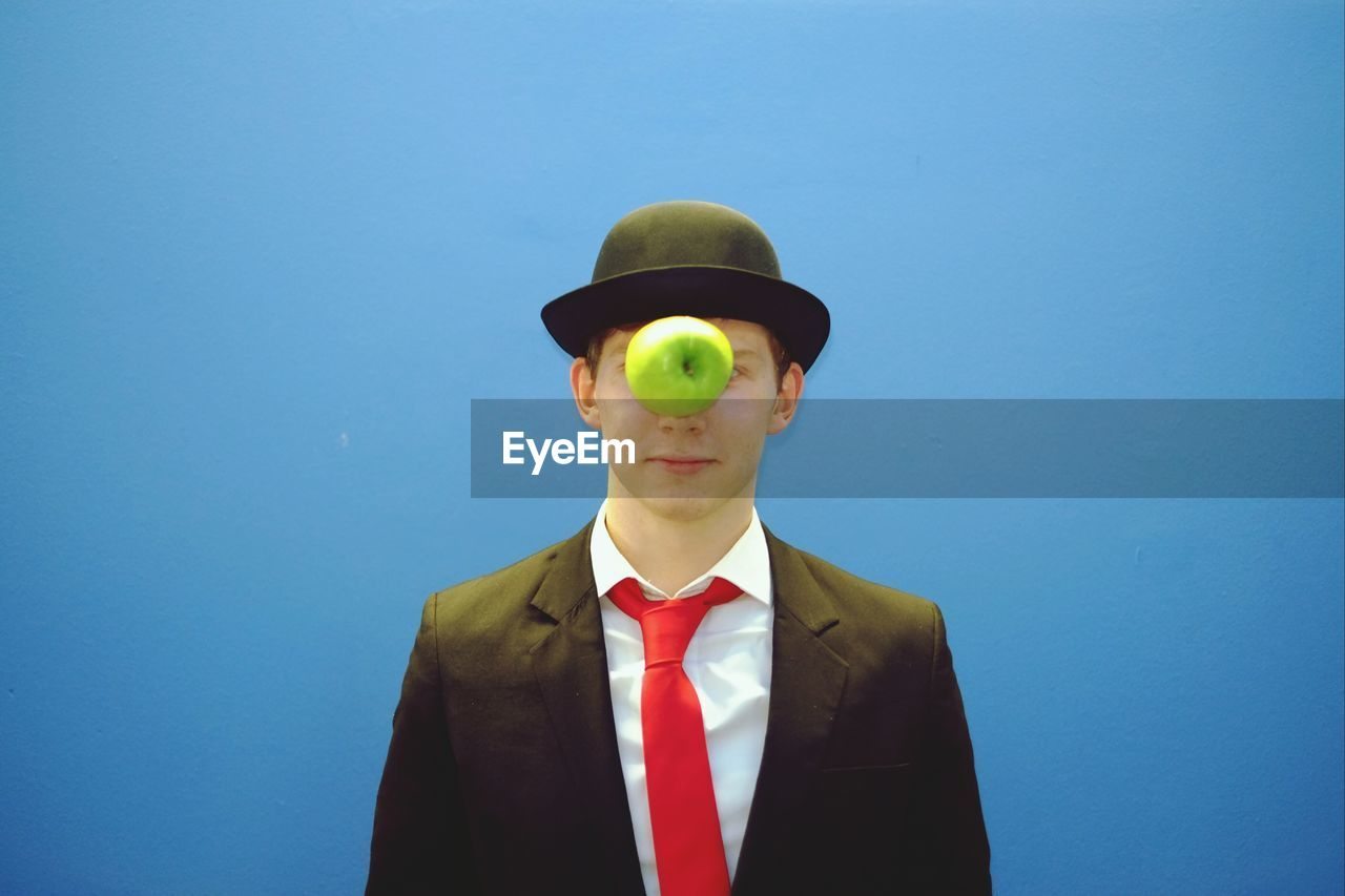 Apple In Front Of Man Face Over Blue Background